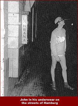 John Lennon stands on a Hamburg street in his underwear. John ventured out into the night on a dare from his mates.