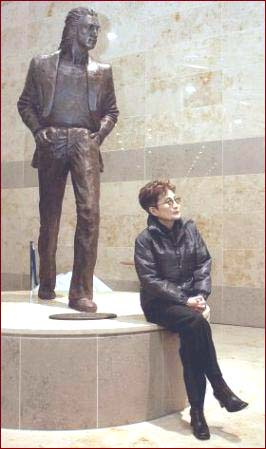 Yoko Ono sits in front of the John Lennon statue at the John Lennon Liverpool Airport.